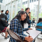 """Phoenix Military Academy student Coraima Sanchez scratches poetry onto a school desk inside the Poetry Foundation during the """"From Within"""" performance."""