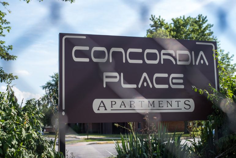 The sign at the entrance of Concordia Place Apartments seen through a chain link fence.
