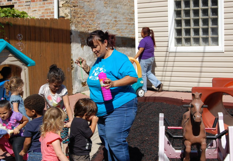 Raquel Irizarry, a head teacher at Little Einstein's Daycare in Logan Square, blows bubbles outside with her class.
