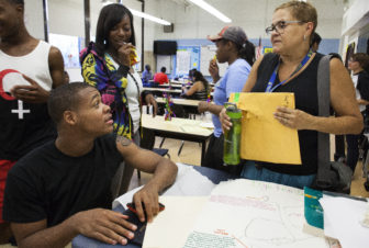 Devante Taylor, 18, (left seated) speaks with Ana Llorens, a career and technical education coordinator, at a Sullivan High School event in August 2014. Sullivan has participated in the district's summer melt initiative the last two years.