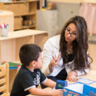 Teacher's aide Claudia Galvez plays the bilingual version of a word-building game with a preschool student at the Guadalupano Family Center in Pilsen earlier this month.
