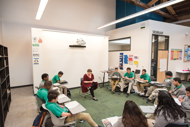 "Ashley Haywood, a ninth-grade English teacher at Intrinsic Schools' Belmont campus, leads a ""Socratic Seminar"" with a small group while her two co-teachers work with other students in a large, open pod. Behind her is a projector mounted to a wall covered in whiteboard paint — which Intrinsic officials say is a cheap alternative to interactive whiteboards."