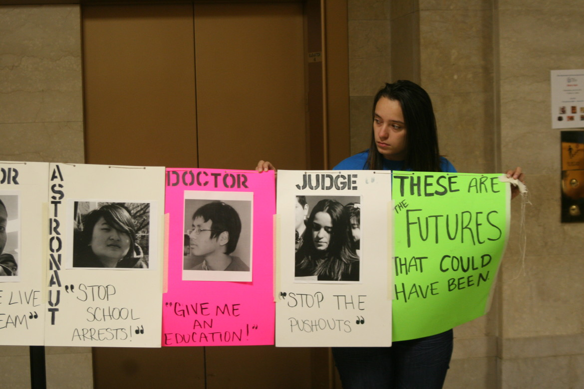 A student member of Voices of Youth in Chicago Education (VOYCE) holds part of a sign representing the 25 young people arrested on CPS property every day.
