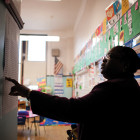 """Gregory Elementary Principal Donella Carter looks at a """"data wall,"""" where teachers track homework completion, test scores and other statistics. Carter says she works to retain her teachers by empowering them and giving them leadership roles. [Photo by Lucio Villa]"""