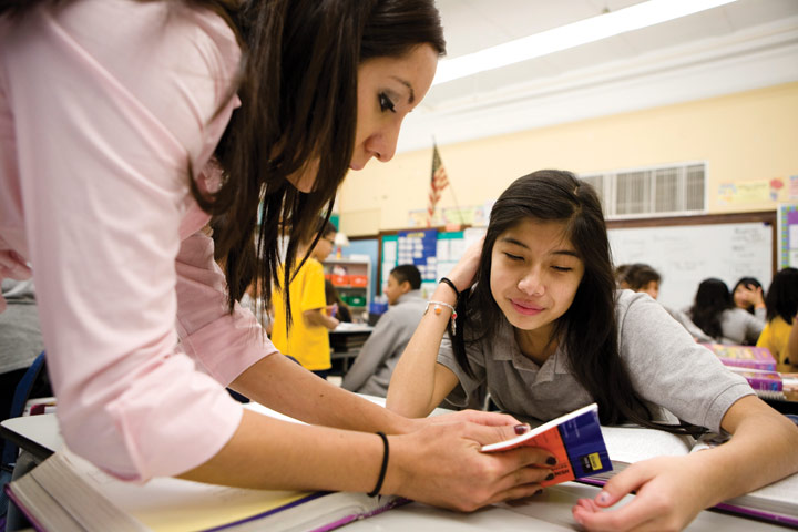 Teacher Elizabeth Carrillo helps 7th-grader Hassuby Castillo in a combined bilingual and general education English class at long-overcrowded Sawyer Elementary.  [Photo by Cristina Rutter]